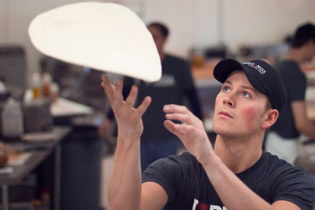 Sean Wise, son of owner Larry Wise, tosses pizza dough in Christianos kitchen